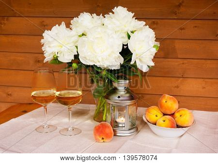 Bouquet of white peonies glasses of wine lantern and peaches