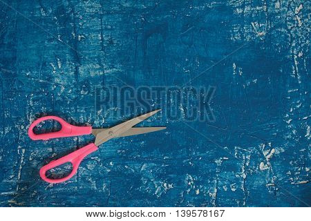 Dark blue background with the pink scissors