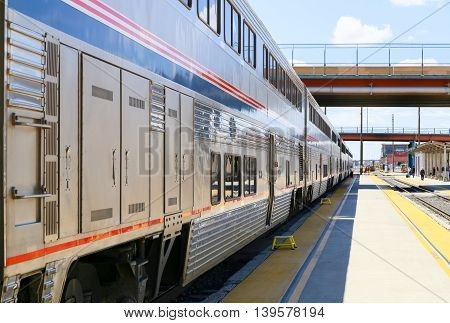 ALBUQUERQUE, USA - MAY 24, 2015: The Amtrak passenger train Southwest Chief stopping with steps placed on the platform in front of the doors to get on the train easier.
