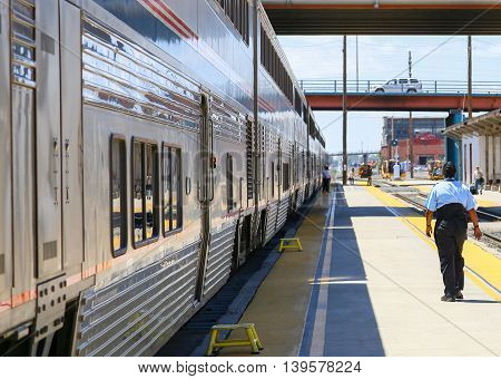 ALBUQUERQUE, USA - MAY 24, 2015: The Amtrak passenger train Southwest Chief at the station. A conductor is walking on the platform next to the train in the back a passenger with a suitcase.