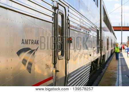 ALBUQUERQUE, USA - MAY 24, 2015: The Amtrak passenger train Southwest Chief ready for departure. The doors are closed and a red lamp is flashing in the back a worker and passengers on the platform.