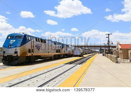 ALBUQUERQUE, USA - MAY 24, 2015: The Amtrak passenger train Southwest Chief at the station. A tanker is parked on the platform next to it a worker and passengers are around.
