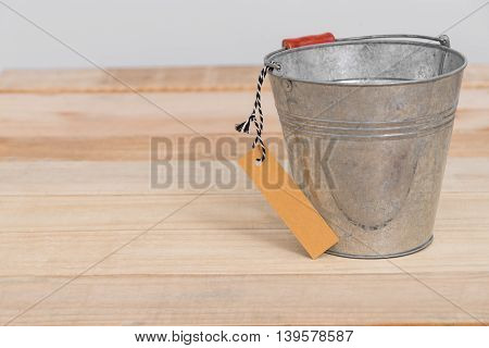 a vintage metal bucket on wooden background with tag