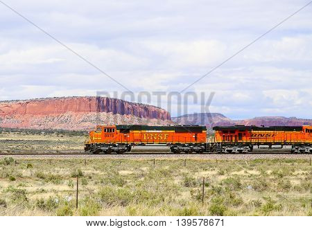 THOREAU, NEW MEXICO, USA - MAY 24, 2015: Two engines of a BNSF freight train on straight track in the desert in front of rock formations.