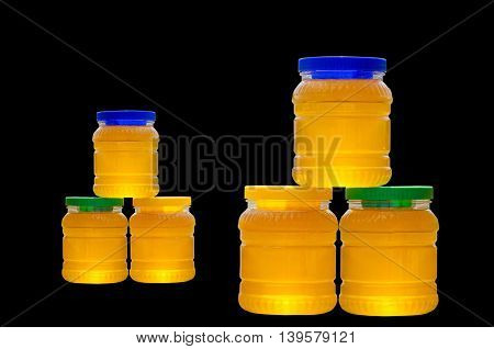 Jars of honey with colorful caps isolated on black background