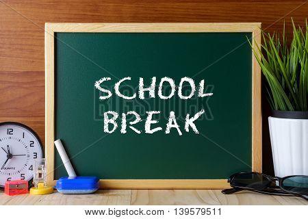 Words School Break Written On Green Chalk Board On Wooden Table.