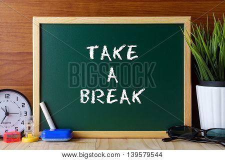 Words Take A Break Written On Green Chalk Board On Wooden Table.