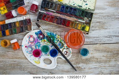 Watercolor paints, brushes and palette on white background. The workplace of the artist. Banner for school