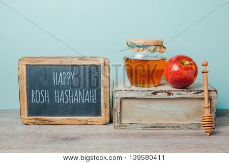 Jewish holiday Rosh Hashana background with chalkboard honey jar and apple on wooden table