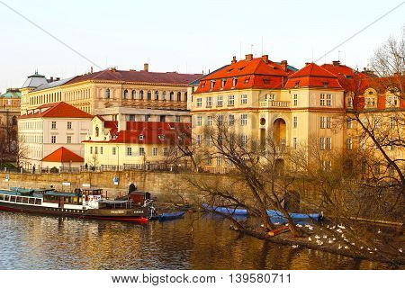 PRAGUE, CZECH REPUBLIC - April 2, 2011: Sun setting over the historical buildings of an art academy and a former monastery next to the Vltava river in Prague. Prague is the capital of the Czech Republic.