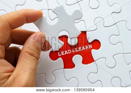 Hand holding a piece of white puzzle with word LEAD AND LEARN.