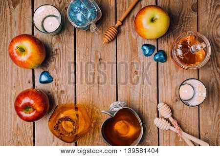 Rosh Hashana holiday background with honey apples and candles on wooden table. View from above. Flat lay