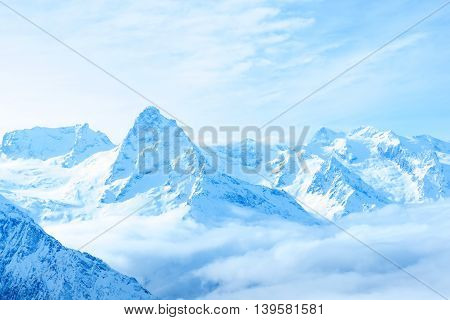 beautiful winter snow covered peaks of Caucasus mountain Dombaj over clouds Russia close up