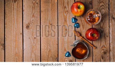 Rosh Hashana holiday background with honey apples and chocolate on wooden table. View from above. Flat lay