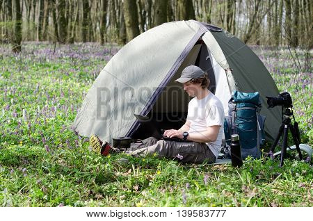 A photographer working on a laptop outdoors in a tent camp.