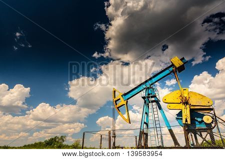 Blue and yellow oil derrick in field under sky with cumulus clouds