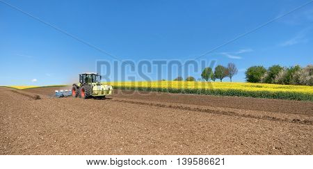 Tractor on a field during sowing, taken in spring in front of a blooming rapeseed field