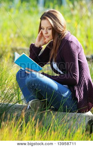 Attractive girl student reading book in autumn park.