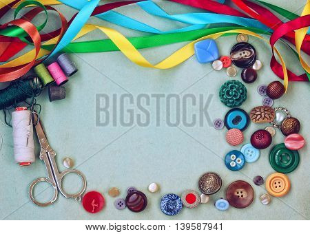 scissors thread needle thimble buttons and variety silk ribbon on old gray cardboard table