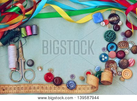 scissors thread needle thimble variety buttons measuring tape and silk ribbon on old gray cardboard table