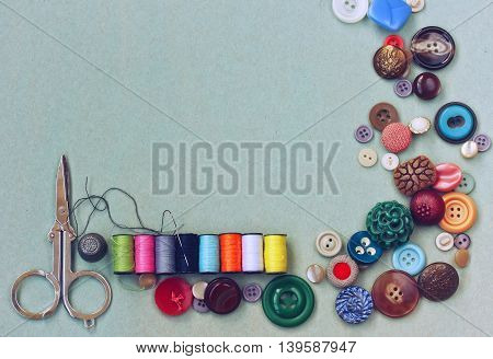scissors thread needle thimble various buttons on old gray cardboard table