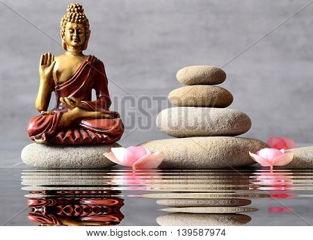 Buddha is sitting in ZEN garden with flower and balance stones.