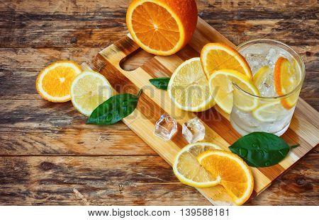orange lemon leaves glass homemade lemonade ice on old wooden table rustic style