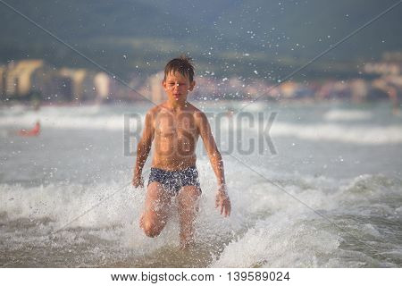 Picture Of Exciting Boy Running On Beach Beside Waves. Image Of Kid In Evening Sunlights On Seaside