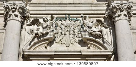 Detail of Santa Maria Assunta baroque church portal with Jesuit symbol between angels