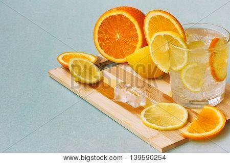 orange lemon glass homemade lemonade and ice on wooden plank on gray cardboard surface