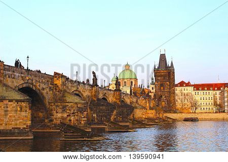 Sun setting over the historical Charles Bridge across the Vltava river in Prague. Prague is the capital of the Czech Republic.