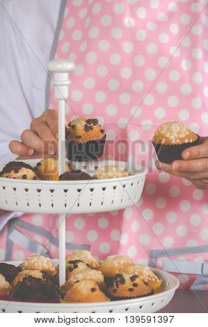 Girl placing various cupcakes on a display