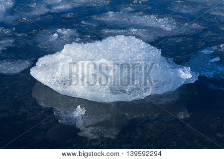 Close up Ice melting in late winter lake, natural Iceland landscape background