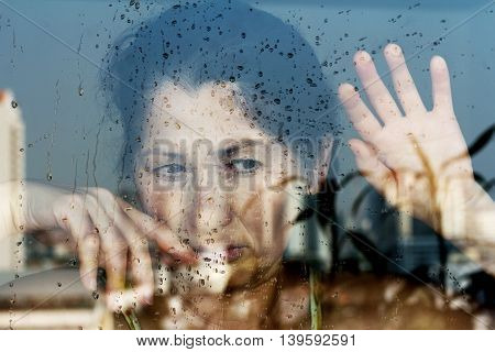 Beautiful 50 years old woman looking through the window