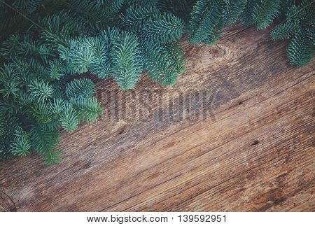 christmas fresh evergreen fir tree branches frame on wood, retro toned