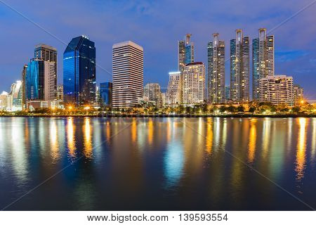 Bangkok City office building with water reflection lights with twilight blue sky background