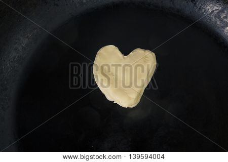 Butter in shape of heart on hot pan - Close up top view