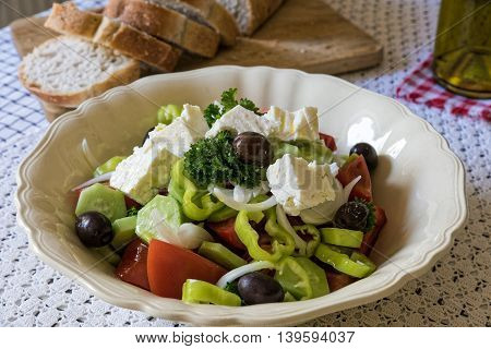 Traditional greek salad, served with bread on table