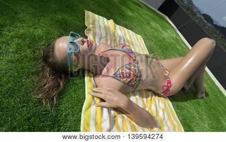 Top view of sexy young woman wearing bikini and blue sunglasses lying on striped beach towel over green grass background