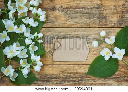 branches delicate jasmine and empty paper tag lie on wooden planks