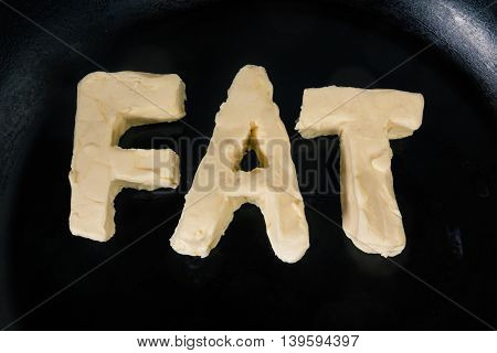 Butter in shape of the word fat on hot pan - Close up top view