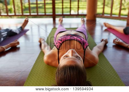 Young Woman In Savasana At Yoga Class