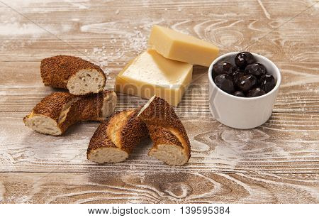 Simit, black olives and yellow cheese on whitewashed wood surface