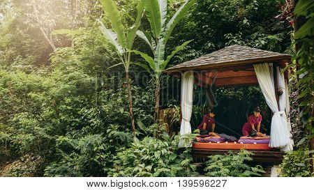 Massage pavilion surrounded by trees with couple receiving body massage. Outdoor spa center at holiday resort.