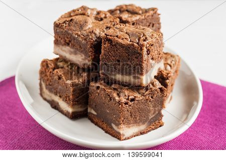 marble chocolate brownies with mascarpone are stacked on a plate.