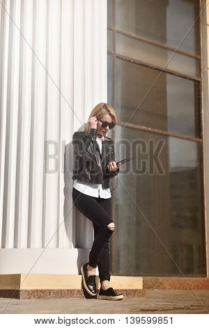 hipster girl with touch pad standing near column and listening music