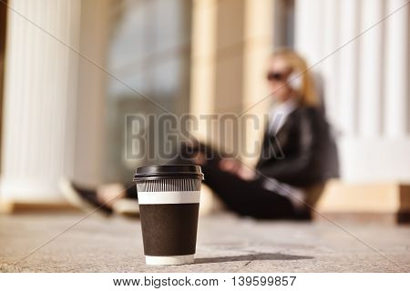 cup of coffee in focus hipster girl with touch pad listening music on background