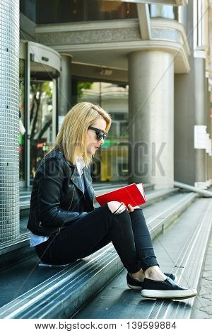 young hipster girl sitting on stairs reading a red book