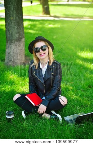 happy hipster girl sitting on grass with book and laptop
