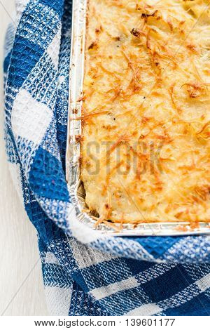 Parmentier casserole in a blue a towel.